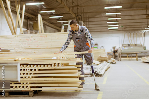 Photo  Disabled young man with an artificial leg is working at furniture factory