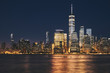 New York City business district skyline at night, color toning applied, USA.