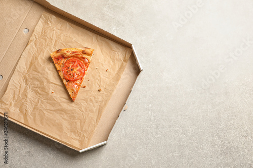 Last slice of cheese pizza in cardboard box on grey table, top view with space for text. Food delivery service
