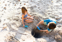 Girl And Boy Digging A Hole In...
