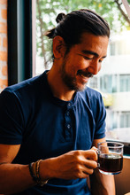 Smiling Mature Man Holding Black Coffee In Cafe