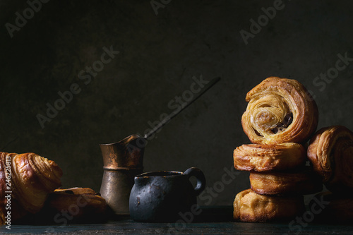 Variety of homemade puff pastry buns cinnamon rolls and croissant served with vintage coffee pot on wooden table Canvas Print
