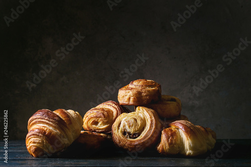 Tela Variety of homemade puff pastry buns cinnamon rolls and croissant on wooden table