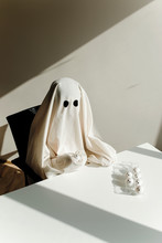 High Angle View Of Man In Ghost Costume With Egg Carton On Table Sitting At Home During Halloween