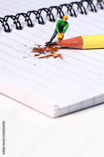 Conceptual diorama image of a miniature figure sharpening a