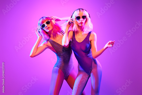 canvas print motiv - evgenij918 : Fashion. Two DJ girl with Dyed Hair in Colorful neon light enjoy music, friends. Party disco 80s 90s vibes. Model woman in fashionable bodysuit, makeup. Creative art style