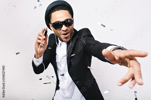 Papiers peints Magasin de musique Portrait expressing brightful positive emotions of handsome guy in hat, suit, black sunglasses having fun in tinsels on white background. Celebrating great party, listening to music, leisure, weekends