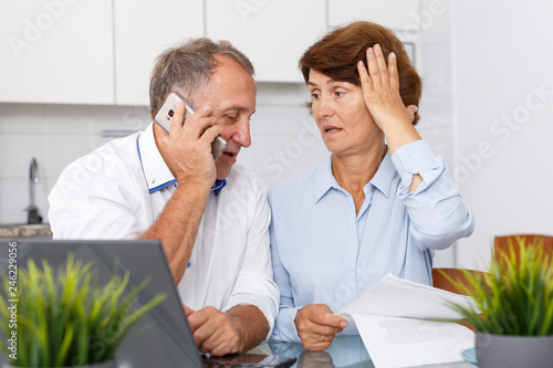 Fotografía  Worried mature family couple with phone sitting at laptop at kitchen table