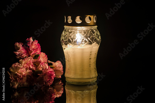 Fotografiet  Lonely burning candle with flowers