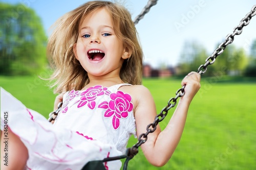 Little child blond girl having fun on a swing