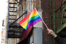 Woman's Hand Waving Rainbow Flag