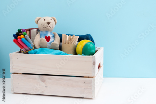 Obraz Wooden box with donations: children's toys, stationery and children's clothing. Concept: you can help, they need help. Background, free space for inscription. Red heart on the chest of a teddy bear. - fototapety do salonu