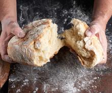 Male Hands Breaking Open Baked...