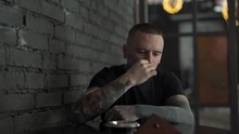 A Handsome Man Fully Covered In Tattoos Finishes Smoking And Butts Out A Cigarette. He Is Thoughtful. The Background Is Blurred.