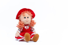 Soft Doll In A Red Dress And Hat On A White Background. Children's Toy. Close-up.