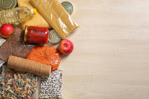 Many different products and space for text on wooden background, flat lay. Food donation