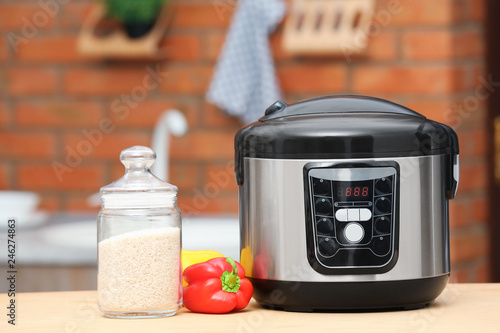 Modern electric multi cooker, jar of rice and peppers on table in kitchen