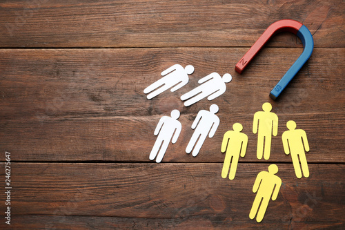 Magnet attracting people traffic on wooden background, top view with space for text Canvas Print