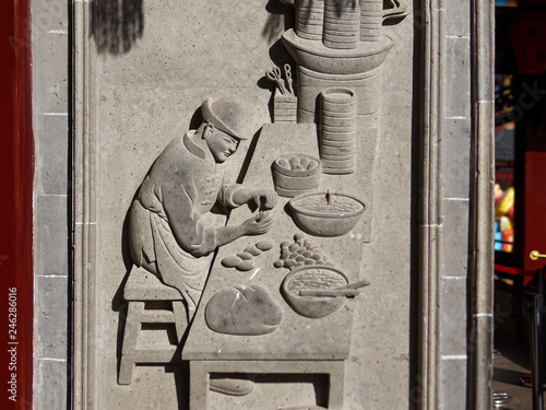 Fotografia  Fine ancient relief on a stone wall showing traditional chinese cooker how to make steamed buns