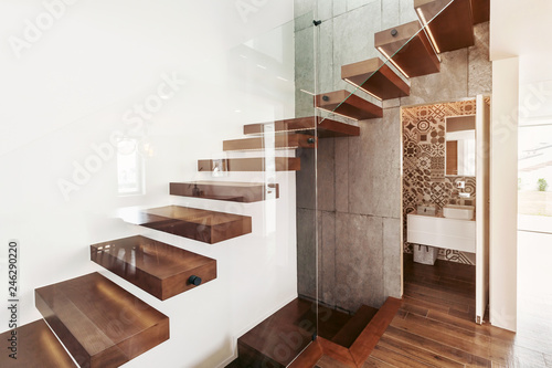 Slika na platnu Stairs in living room with open door to bathroom and glass wall