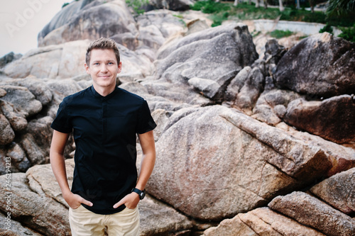 Outdoor Portrait of Young smiling businessman wearing black shirt standing on ri Tablou Canvas