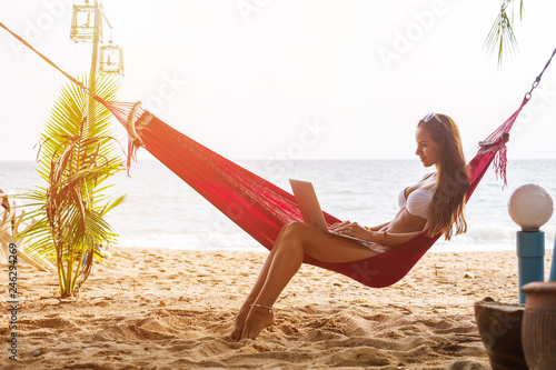 Fotomural Young woman working on laptop seating in hammock under palm trees on tropical be