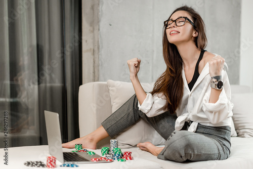 Fotomural Stylish young brunette girl betting and playing poker online on laptop, winning