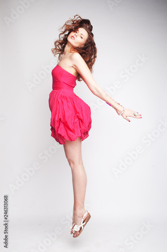 Obraz na plátně Young charming female in pink chiffon dress jumping over grey background