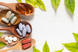 Leinwandbild Motiv Variety of vitamin pills in wooden spoon on white background with green leaf, supplemental and healthcare product, flat lay surface