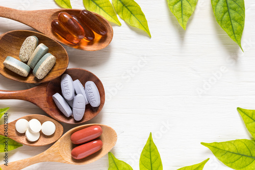 Stampa su Tela  Variety of vitamin pills in wooden spoon on white background with green leaf, su