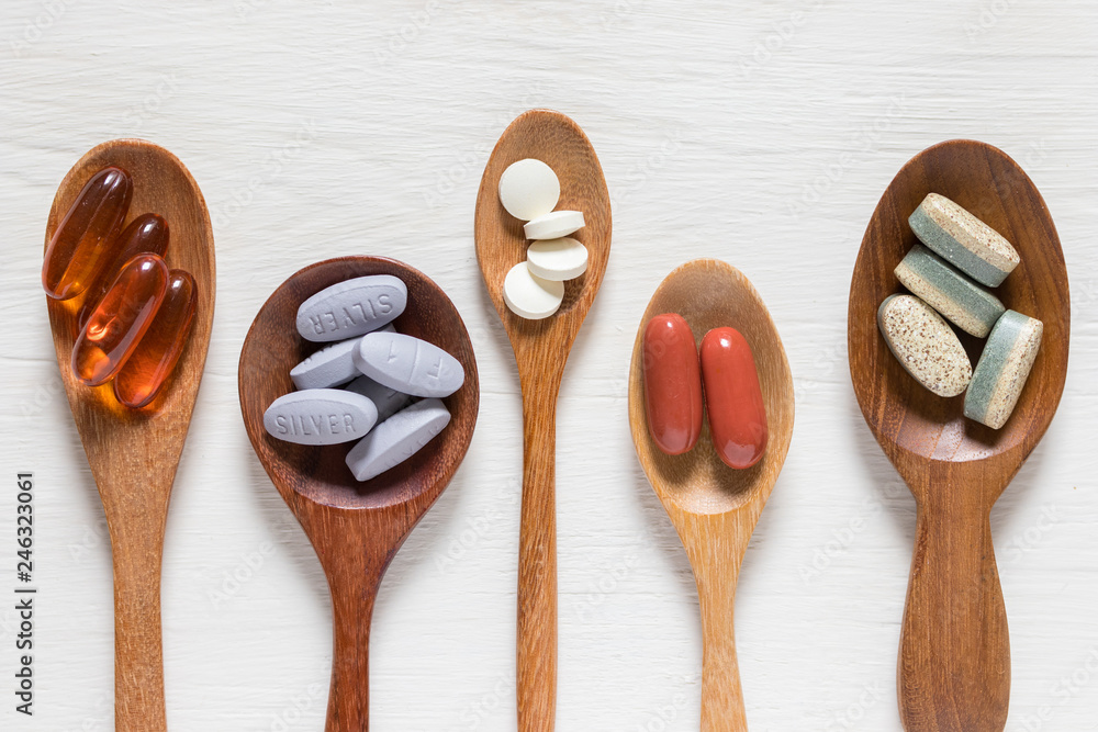 Fototapeta Variety of vitamin pills in wooden spoon on white background, supplemental and healthcare product, flat lay surface