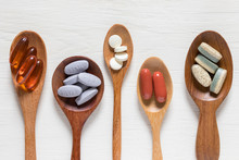 Variety Of Vitamin Pills In Wooden Spoon On White Background, Supplemental And Healthcare Product, Flat Lay Surface
