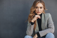 Portrait Of Beautiful Woman With Long Curly Blond Hair Outdoors In Spring. Young Woman With Natural Makeup In A Gray Jacket . A Smart Photo Of A Young Beautiful Woman In Autumn Clothes.