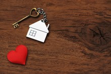 House Key With Home Keyring Decorated With Mini Red Heart On Wood Texture Background, Sweet Home Concept