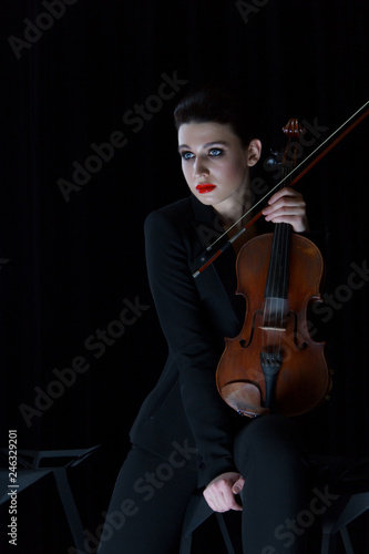 Spoed Fotobehang Muziek violin and girl playing, cello on dark background, red lips, brunette