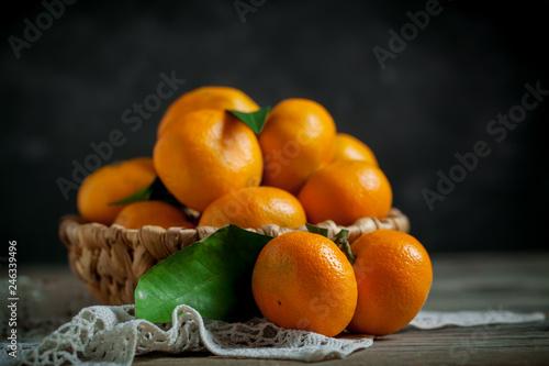 Fototapeta  Tangerines with leaves in basket on rustic wooden background.