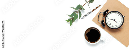 Flat lay cup of black coffee, black alarm clock, notebook, diary, eucalyptus on white background top view copy space. Minimalistic food concept, Feminine desk workspace, time to work coffee background