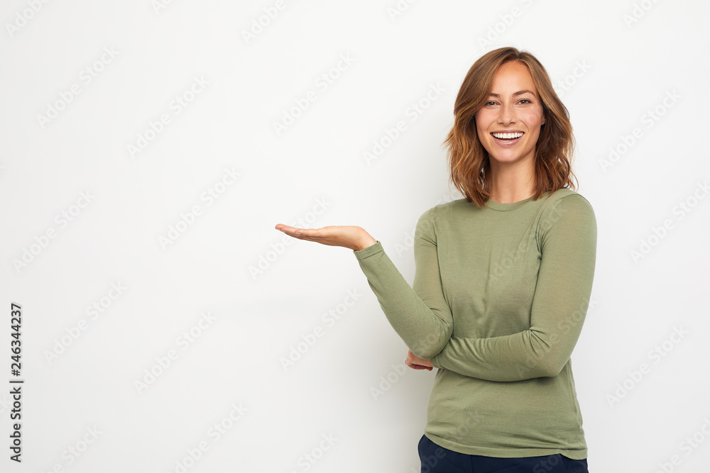 Fototapeta young happy woman presenting your product on thie background