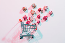 Womens Day Flower Delivery. Empty Shopping Cart With Falling Roses. Ivory Background With Red Shadows.