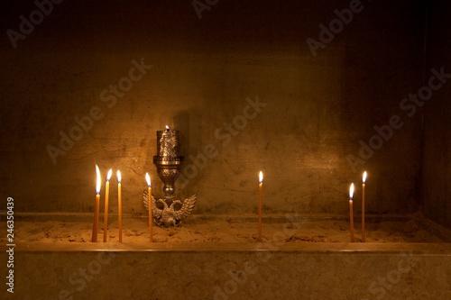 Fotografia  Lit candles candle light and a golden vigil oil lamp kept permanently burning pl