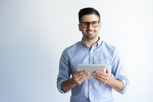 Portrait Of Cheerful Excited Tablet User Wearing Eyeglasses. Young Caucasian Man In Casual Holding Tablet And Smiling At Camera. Mobile Internet Concept