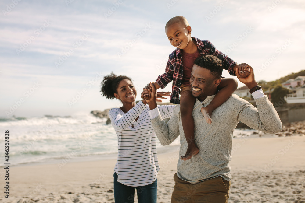 Fototapety, obrazy: Parents carrying son on shoulders on beach vacation