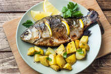 Baked Fish Carp With Lemon Greens And Potatoes On A Plate. Wooden Background.