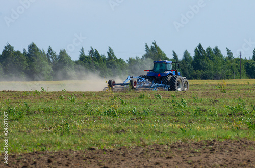 Fotografie, Obraz  Blue tractor plowing the green field with an iron harrow in the plowing season w