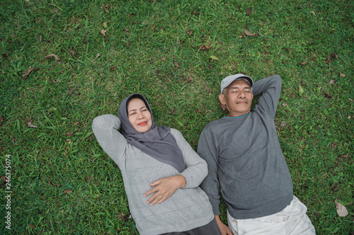 Fotografie, Obraz  senior asian muslim couple laying down on grass