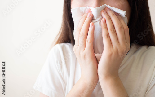 Fényképezés  Young woman​ sneezing and blowing her nose w/ tissue​ paper