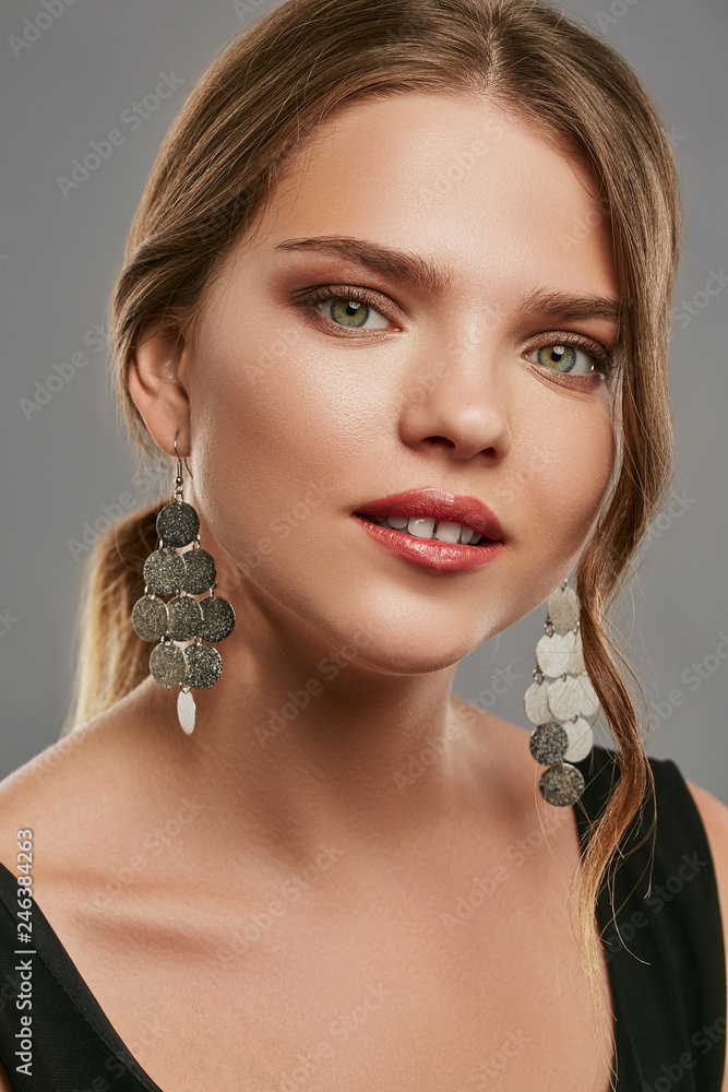 Fototapeta A portrait of a Caucasian lady with natural makeup and red lipstick, wearing a black sports shirt and long dangle earrings. The woman with brown hair is on gray background, looking at the camera.