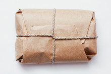 Box Parcel Wrapped In Brown Craft Paper   Tied Hemp Cord On White Background.