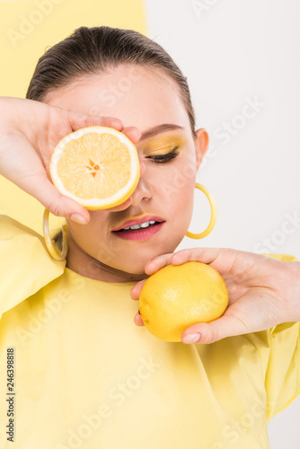 Fototapety, obrazy: selective focus of beautiful stylish girl holding lemons and posing with limelight on background