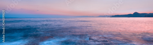Beautiful mysterious marine landscape at sunset. Mountains, volcanic reef and ocean, panoramic banner.